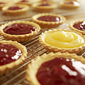 Close Up Of Jam Tarts Cooling On Wire Racks by Adam Gault