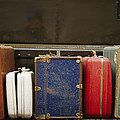 Colorful But Worn Luggage Awaits by Raul Touzon