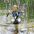 Cute Tiny Boy Riding A Duck by Jaroslaw Grudzinski