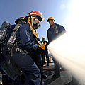 Damage Controlmen Conduct Fire Hose by Stocktrek Images