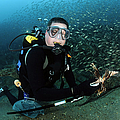 Diver Collects Invasive Lionfish by Karen Doody