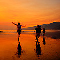 Family Running In The Beach At Sunset by Jorge Fajl