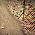 Footprints On The Beach Along A Fence by Randall Nyhof