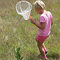 Girl Collecting Insects In A Meadow by Ted Kinsman