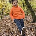 Girl Kicking Leaves by Ian Boddy