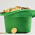 Green Hat Filled With Golden Coins by Vstock LLC