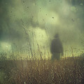 Hooded Man Walking In Field With Storm Clouds by Sandra Cunningham