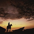 Horseback Rider Silhouetted On A Beach by Michael Melford