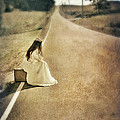 Lady In Gown Sitting By Road On Suitcase by Jill Battaglia
