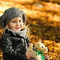Little Girl In Autumn Leaves by Waldek Dabrowski