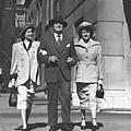 Man And Two Women Walking On Sidewalk, (b&w) by George Marks