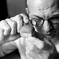 Man Looking At Miniture Loaf Of Bread Through Magnifying Glass by Hulton Archive