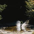 Mountain Biker Splashing Through Water by Skip Brown