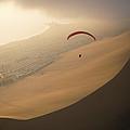 Ocean Gusts Keep A Paraglider Aloft by Joel Sartore