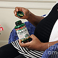 Pregnant Woman Taking Fish Oil by Photo Researchers