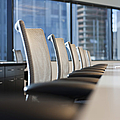 Row Of Chairs And A Table In A Conference Room by Jetta Productions, Inc