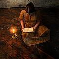 Schoolgirl Sitting On Wood Floor Reading By Candlelight by Jill Battaglia