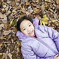 Smiling Girl Lying On Autumn Leaves by Ian Boddy