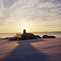 Snow Covered Field With Farm Silhouette At Sunset by Jeremy Woodhouse