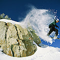 Snowboarder Jumping Off A Big Rock by Skip Brown