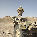 Soldier Climbs A Damaged Husky Tactical by Stocktrek Images