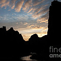 Sunset With Rugged Cliffs In Silhouette by Karen Lee Ensley
