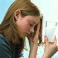 Teenager With Headache Holds Dissolving Painkiller by Damien Lovegrove