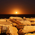 The Moon Rising Behind Rocks Lit by Luis Argerich