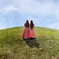 Two Girls In Vintage Dresses Walking Up Grassy Hill by Jill Battaglia