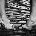 Two Young Women Wearing High Heeled Shoes And Fake Tan On Cobblestones On A Night Out by Joe Fox