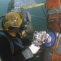 U.s. Navy Diver Uses A Grinder To File by Stocktrek Images
