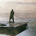 Villager On Raft Crosses Lake Phewa Tal by Gordon Wiltsie