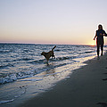 Woman And Dog Running On Beach, Nags by Skip Brown