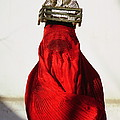 Woman Draped In Red Chadri Carries by Thomas J Abercrombie