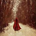 Woman With Red Cape Walking In Woods by Sandra Cunningham