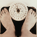 Woman's Feet On A Set Of Weighing Scales by Cristina Pedrazzini