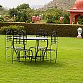 Wrought Metal Chairs Around A Table In A Lawn by Ashish Agarwal