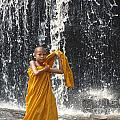 Young Monk In Front Of Waterfall by Jarrod Brown