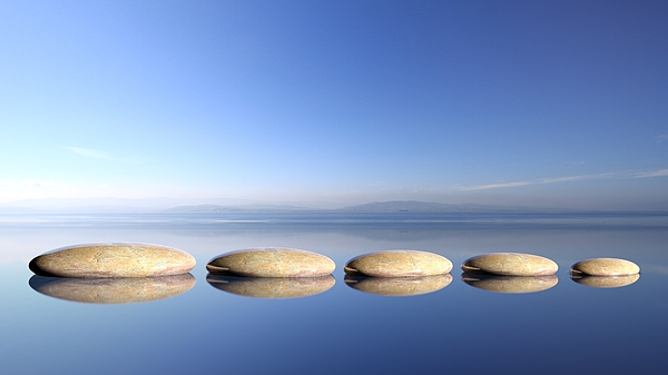 Zen Stones Row From Large To Small In Water With Blue Sky And