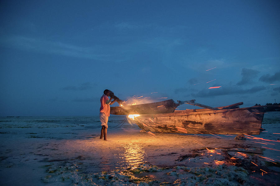 A local fisherman uses flame to repair his boat at sunset by Gareth Pickering