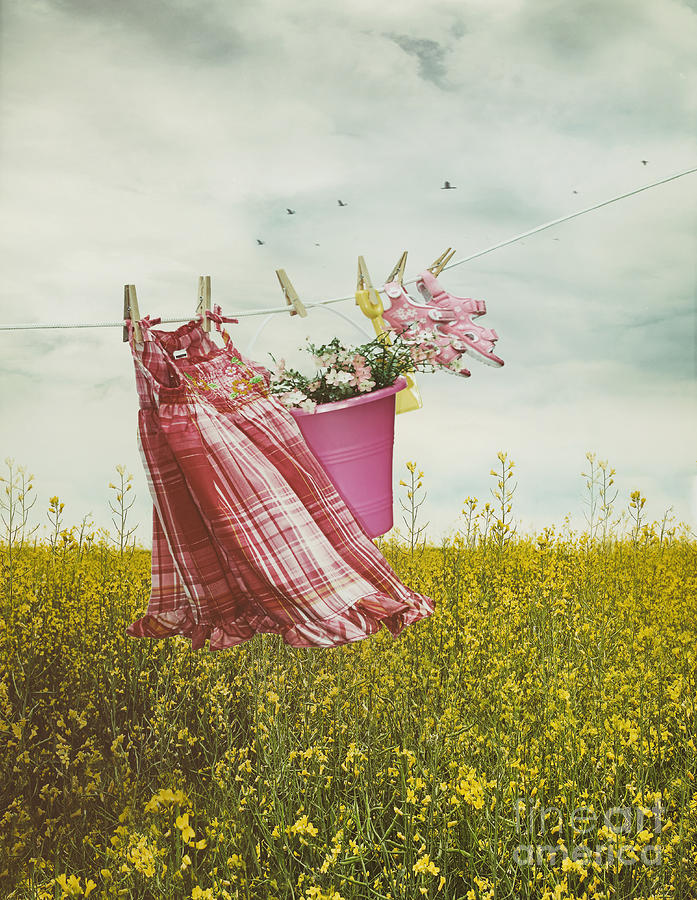 Atmosphere Photograph - Childs Dress And Toys Hanging On Line With Farmhouse In Backgro by Sandra Cunningham