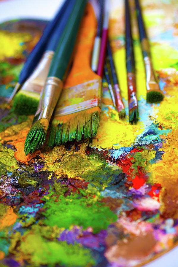 Paint brushes to the painting palette with colors on a ...