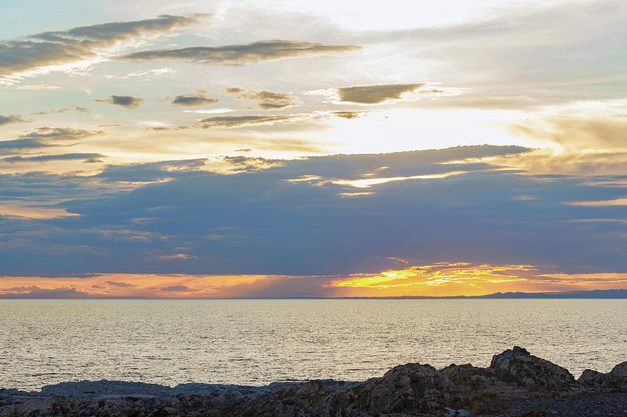 Dark Fluffy Clouds On Sky Over Sea During Fiery Sunset by Oleg Yermolov