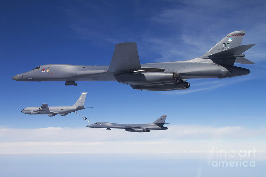 Military Photograph - A B-1b Lancer Stands By As Another by Stocktrek Images