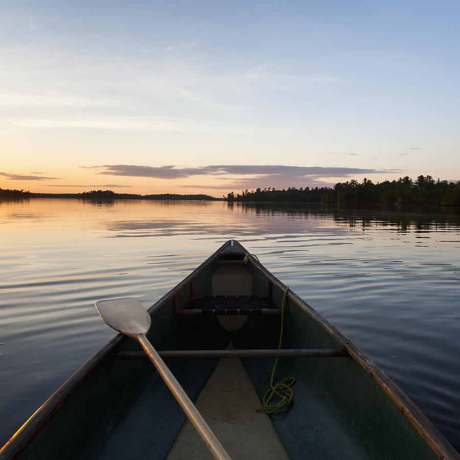 A Boat And Paddle On A Tranquil Lake Photograph by Keith Levit
