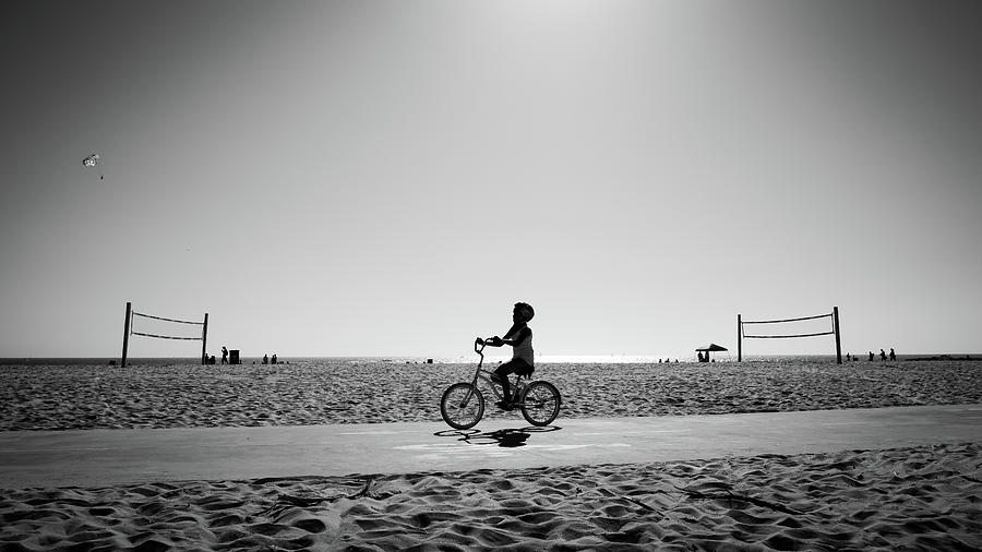 Beach photograph a boy cycling in venice beach los angeles united states