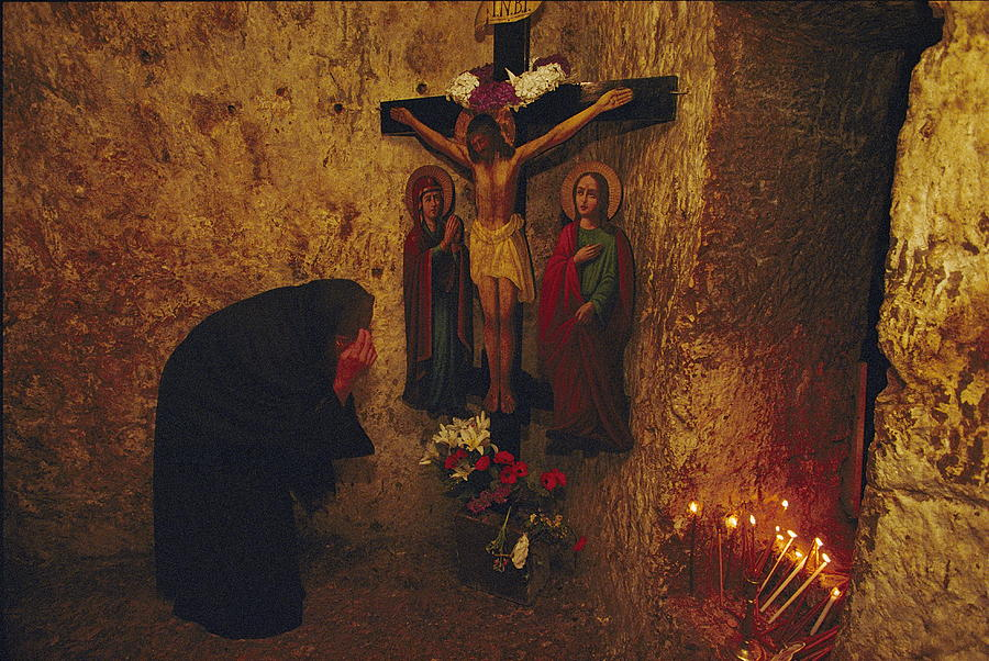 Color Image Photograph - A Greek Pilgrim Prays In The Grotto by Annie Griffiths