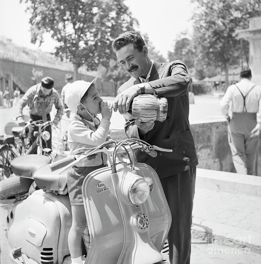 Rome Photograph - A man and his son on a 1955 Lambretta scooter, drinking water at by The Harrington Collection