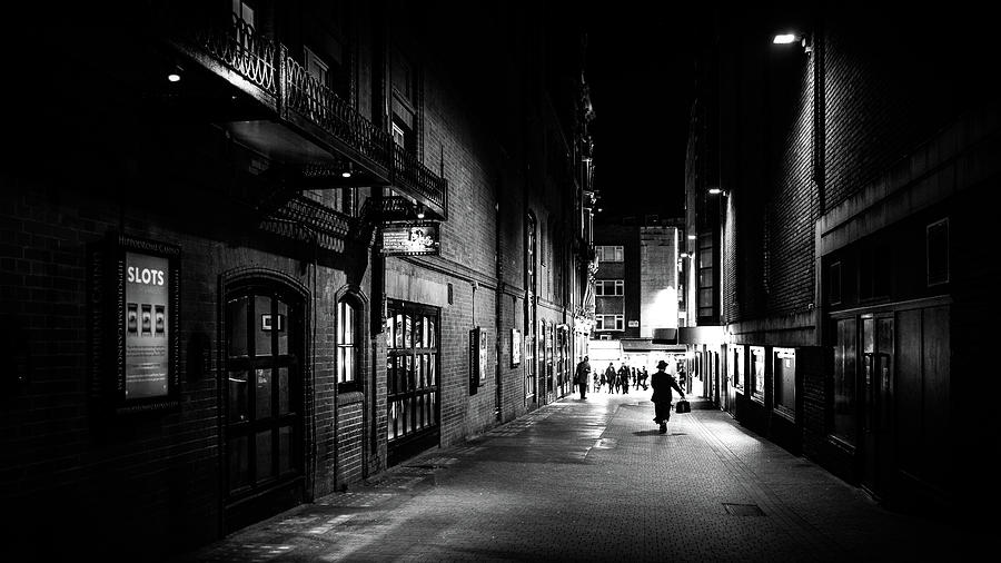 Black photograph a man walking at night london england black and white