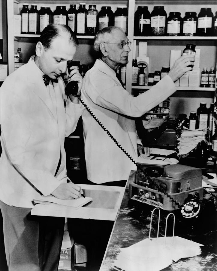 History Photograph - A Pharmacist Demonstrates The Use Of An by Everett